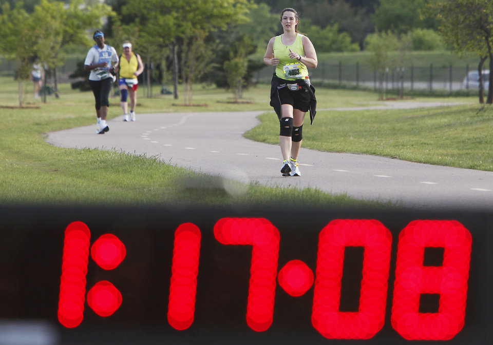 Photo - Runners pass a clock near the halfway point during the Tenth Annual Oklahoma City Memorial Marathon, Sunday, April 25, 2010.  Photo by David McDaniel, The Oklahoman ORG XMIT: KOD