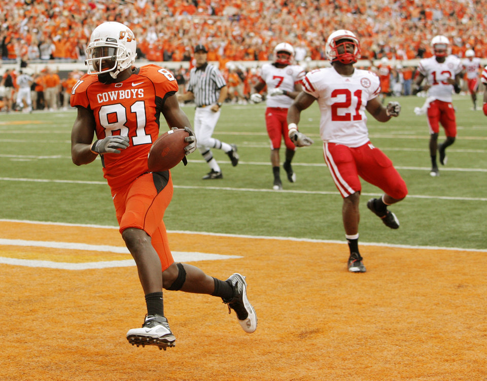 Photo - OSU's Justin Blackmon (81) scores on an 80-yard touchdown catch in front of Nebraska's DeJon Gomes (7), Prince Amukamara (21) and P.J. Smith (13) in the second quarter during the college football game between the Oklahoma State Cowboys (OSU) and the Nebraska Huskers (NU) at Boone Pickens Stadium in Stillwater, Okla., Saturday, Oct. 23, 2010. Photo by Nate Billings, The Oklahoman