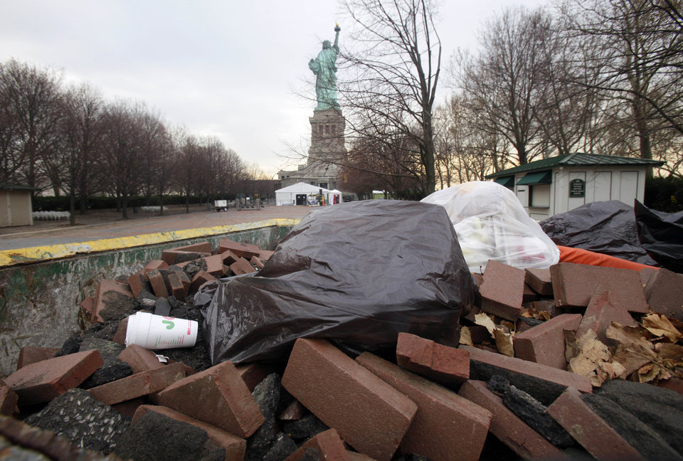 Photo - Bricks from the walkway that surrounds Liberty Island are collected in a Dumpster, in New York,  Friday, Nov. 30, 2012. Tourists in New York will miss out for a while on one of the hallmarks of a visit to New York, seeing the Statue of Liberty up close. Though the statue itself survived Superstorm Sandy intact, damage to buildings and Liberty Island's power and heating systems means the island will remain closed for now, and authorities don't have an estimate on when it will reopen. (AP Photo/Richard Drew)