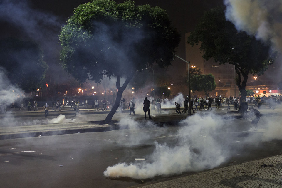 Photo - People run from tear gas during a protest in Rio de Janeiro, Brazil, Thursday, June 20, 2013.  More than half a million Brazilians poured into the streets of at least 80 Brazilian cities Thursday in demonstrations that saw violent clashes and renewed calls for an end to government corruption and demands for better public services. Riot police battled protesters in at least five cities, with some of the most intense clashes happening in Rio de Janeiro, where an estimated 300,000 demonstrators swarmed into the seaside city's central area. (AP Photo/Felipe Dana)