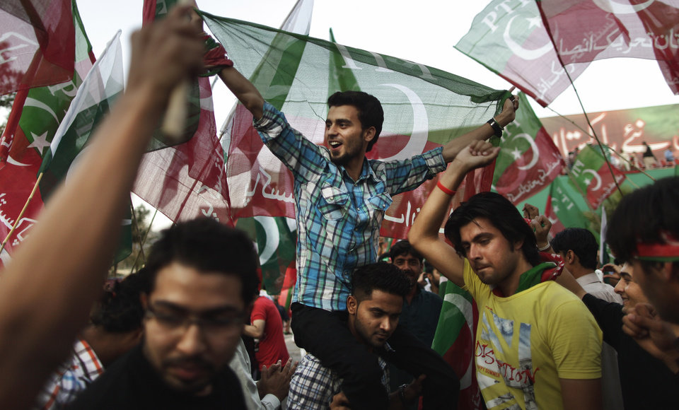 Photo - Pakistani supporters of former cricket star-turned-politician, and leader of Pakistan Tehreek-e-Insaf party, Imran Khan, chant slogans during a rally in support of Khan in Islamabad, Pakistan, Thursday, May 9, 2013. Pakistan is scheduled to hold parliamentary elections on May 11, the first transition between democratically elected governments in a country that has experienced three military coups and constant political instability since its creation in 1947. The parliament's ability to complete its five-year term has been hailed as a significant achievement. (AP Photo/Muhammed Muheisen)