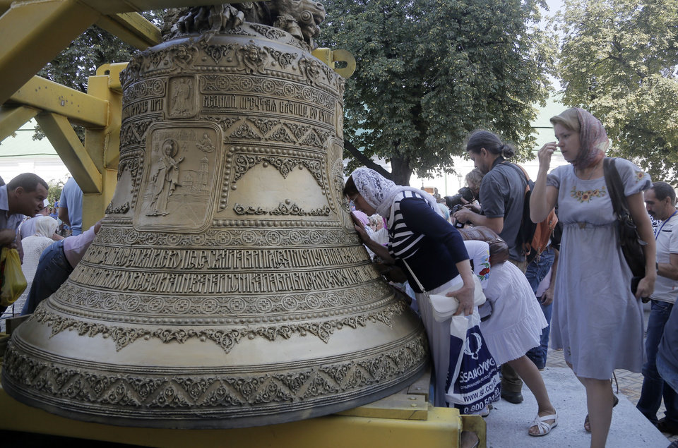 Photo - Ukrainian people kiss the new bell and pray near it, before it is lifted into place, set in the main bell tower of the golden domed Orthodox Monastery of Caves in Kiev, Ukraine, Tuesday, Aug. 19, 2014.  The bell weighs 7,150 kilograms and is decorated with a unique decor, made in Ukraine.  (AP Photo/Efrem Lukatsky)