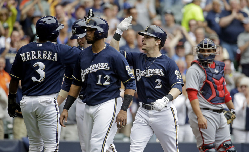 Photo - Washington Nationals catcher Sandy Leon watches as Milwaukee Brewers' Scooter Gennett (2)  is congratulated at home by Elian Herrera (3) after hitting a grand slam during the second inning of a baseball game Wednesday, June 25, 2014, in Milwaukee. (AP Photo/Morry Gash)