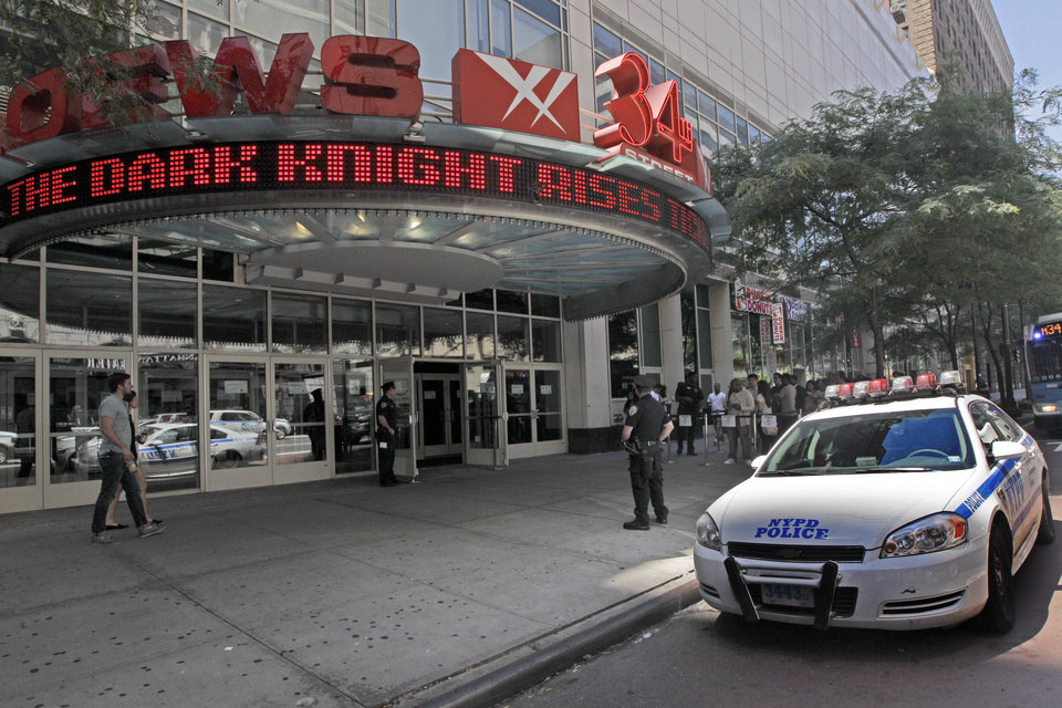 Photo -   Police officers stand guard as people line up for a screening of the new Batman movie at a theatre in midtown, Saturday, July 21, 2012 in New York. Security was stepped up in theatres around the U.S. during showings of the new Batman movie,
