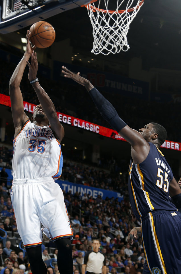 Photo - Oklahoma City's Kevin Durant (35) shoots a lay up as Indiana's Roy Hibbert (55) defends during the NBA game between the Oklahoma City Thunder and the Indiana Pacers at the Chesapeake Energy Arena, Sunday, Dec. 8, 2013. Photo by Sarah Phipps, The Oklahoman