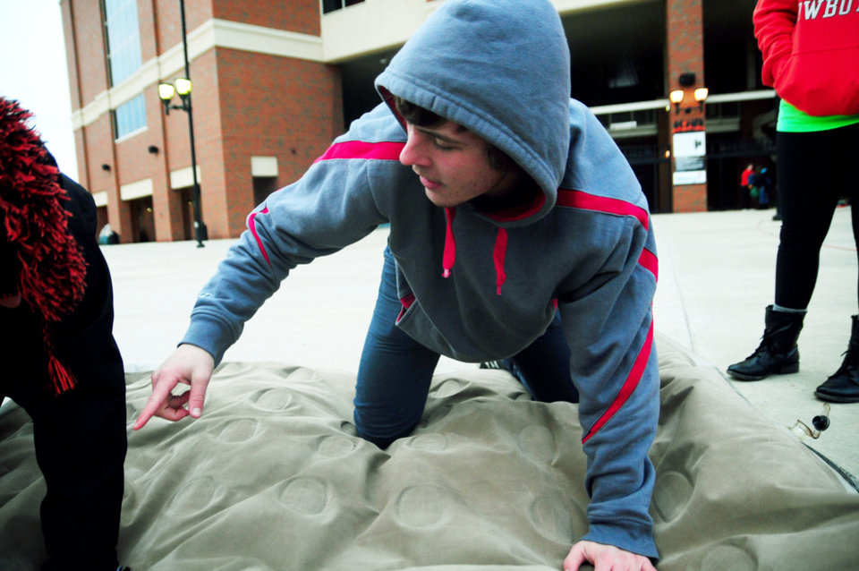 Photo - Oklahoma State student James Harber deflates an air matress after tearing down his group's tent at Boone Pickens Stadium on Dec. 4, 2013 in Stillwater, Okla. Frigid weather caused officials to cancel camping out for early entry to the December 7 Bedlam football game. Photo by KT King/For the Oklahoman