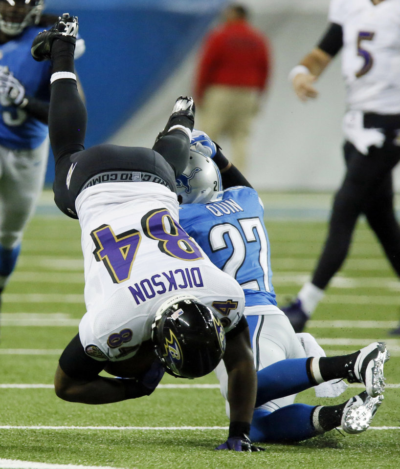 Photo - Baltimore Ravens tight end Ed Dickson (84) is upended by Detroit Lions strong safety Glover Quin (27) during the second quarter of an NFL football game in Detroit, Monday, Dec. 16, 2013. (AP Photo/Duane Burleson)