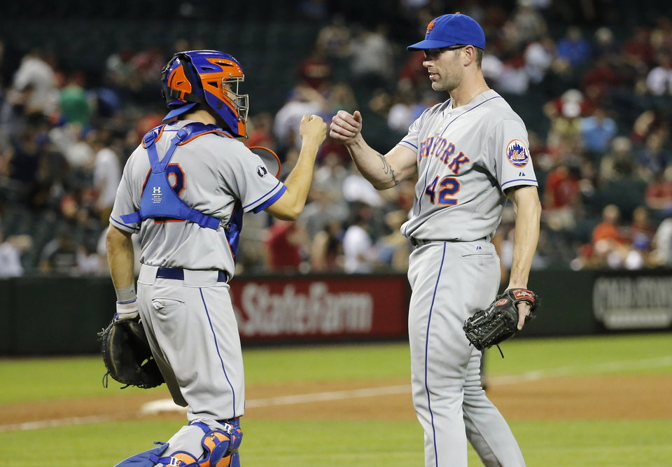 Photo - New York Mets' Kyle Farnsworth, right, knuckles catcher Travis d'Arnaud after a baseball game against the Arizona Diamondbacks on Tuesday, April 15, 2014, in Phoenix. The Mets won 9-0. (AP Photo/Matt York)