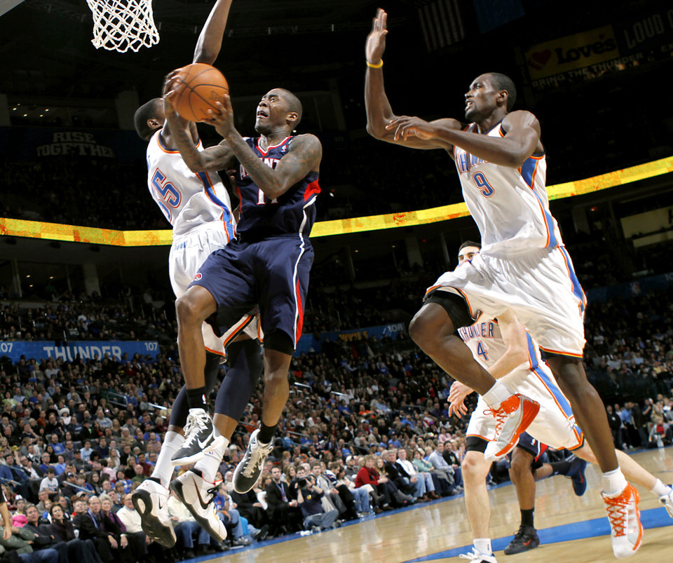 Photo - Atlanta's  Jamal Crawford collides with Kevin Durant as he puts up a shot in front of Durant and Sere Ibaka during their NBA basketball game at the OKC Arena in Oklahoma City on Friday, Dec. 31, 2010. The Thunder beat the Hawks 103-94. Photo by John Clanton, The Oklahoman