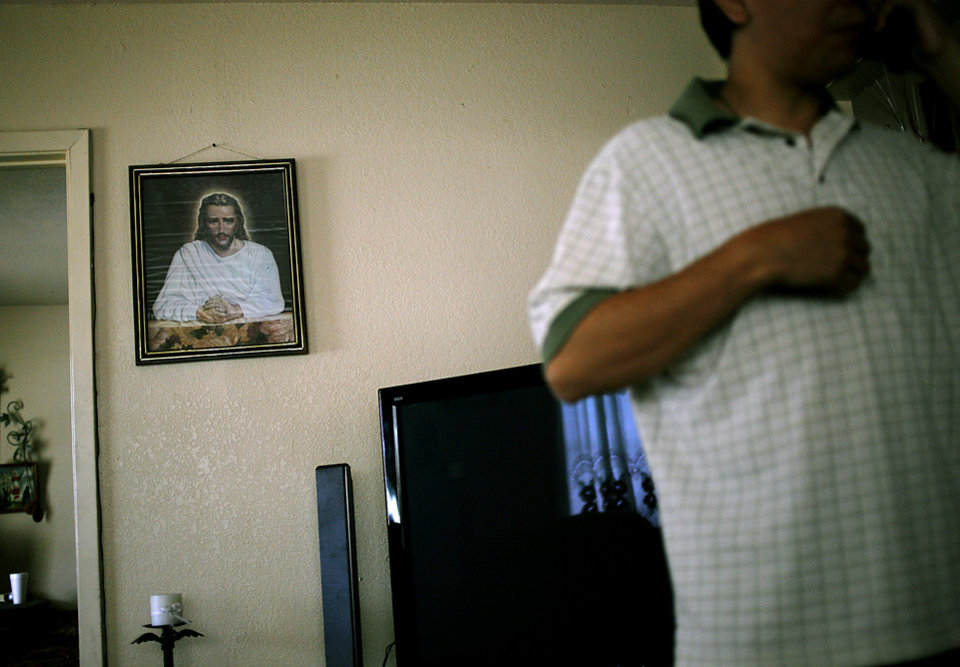 Photo - UNDOCUMENTED WORKER / ILLEGAL IMMIGRATION / IMMIGRANT:  Standing in his living room, Gabriel talks on the phone with a friend in Oklahoma City on Sunday, May 23, 2010. Photo by John Clanton, The Oklahoman ORG XMIT: KOD