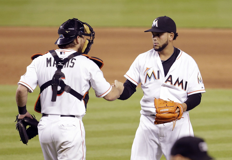 Photo - Miami Marlins starting pitcher Henderson Alvarez, right, shakes hands with catcher Jeff Mathis (6) after Alvarez pitched a complete game and the Marlins defeated the Tampa Bay Rays 1-0 in an interleague baseball game, Tuesday, June 3, 2014, in Miami. (AP Photo/Lynne Sladky)