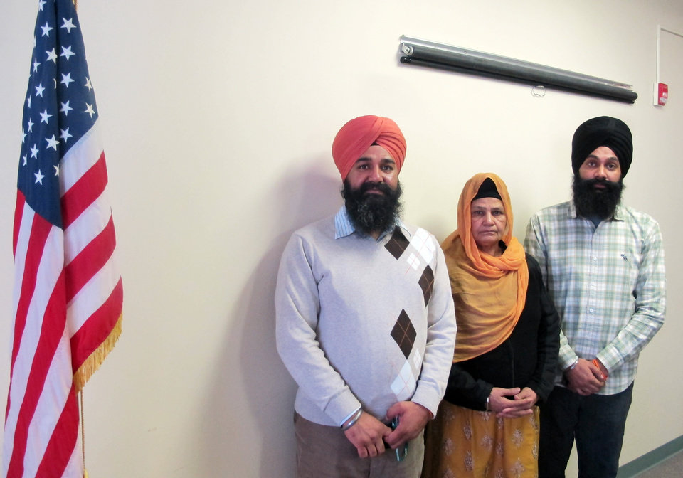 Photo - In this Jan 16, 2013 photo, Kulwant Kaur, wife of Punjab Singh, poses with her sons Raghuvinder Singh, left, and Jaspreet Singh in a conference room at the long-term care facility in Wisconsin where Punjab Singh is recovering. Punjab was critically injured in a shooting rampage at a Sikh temple in Oak Creek, Wis., in August 2012, that left six people dead. Kulwant and her sons watched over the 65-year-old Sikh priest 24 hours a day at the facility where he remained largely unresponsive until January 2013, when he began showing signs of cognitive improvement. (AP Photo/Dinesh Ramde)