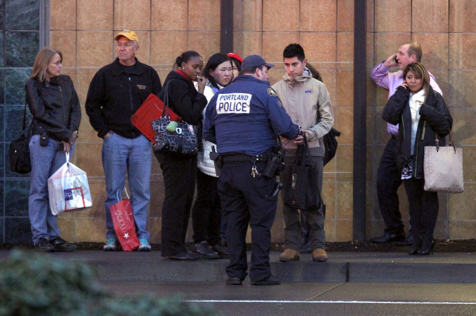 Photo - CORRECTS MALL LOCATION - A police officer conducts interviews with mall patrons outside the Clackamas Town Center in Portland, Ore. Tuesday, Dec. 11, 2012. A gunman is dead after opening fire in the Portland, Ore., area shopping mall Tuesday, killing two people and wounding another, sheriff's deputies said. (AP Photo/The Oregonian, Bruce Ely)  MAGS OUT; TV OUT; LOCAL TV OUT; LOCAL INTERNET OUT; THE MERCURY OUT; WILLAMETTE WEEK OUT; PAMPLIN MEDIA GROUP OUT