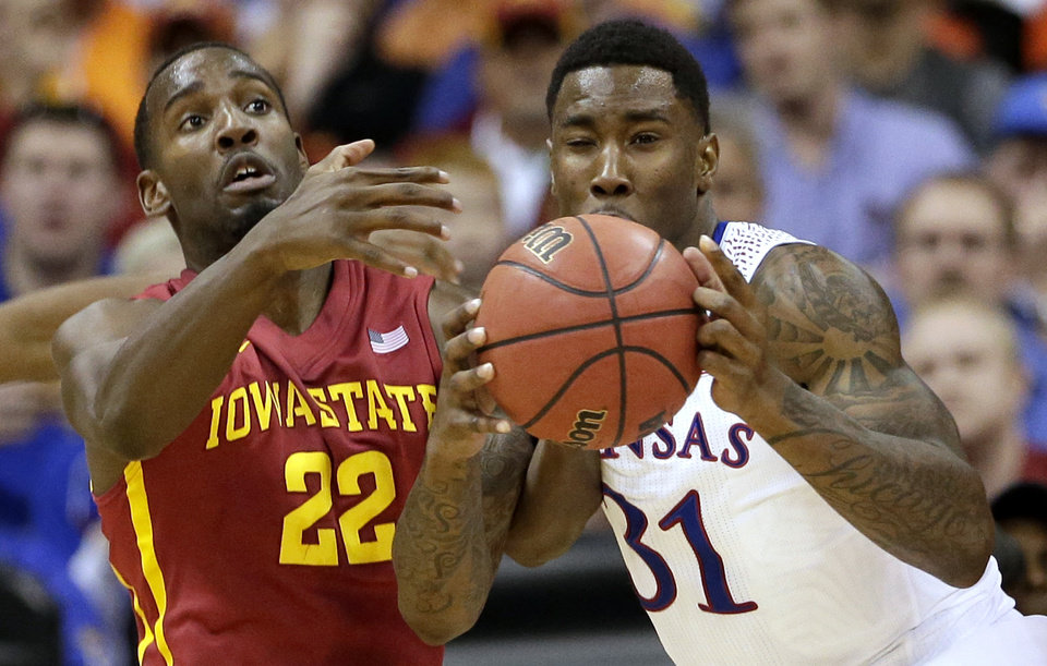 Photo - Iowa State's Dustin Hogue (22) and Kansas' Jamari Traylor (31) battle for a rebound during the first half of an NCAA college basketball game in the Big 12 men's tournament on Friday, March 14, 2014, in Kansas City, Mo. (AP Photo/Charlie Riedel)