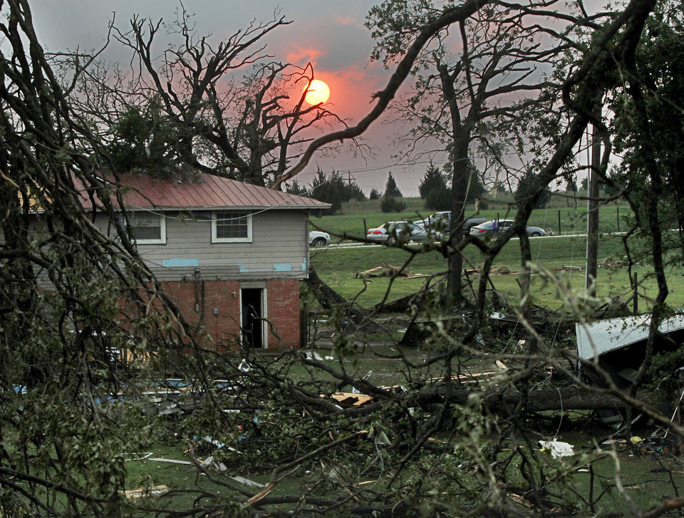 A beautiful sunset is seen through the mangled trees on the property of this home along US 177 that was heavily damaged by the tornado. A tornado caused extensive damage along I-40 at the junction with US 177 on the west side of Shawnee Sunday evening, May 19, 2013. Photo by Jim Beckel, The Oklahoman.