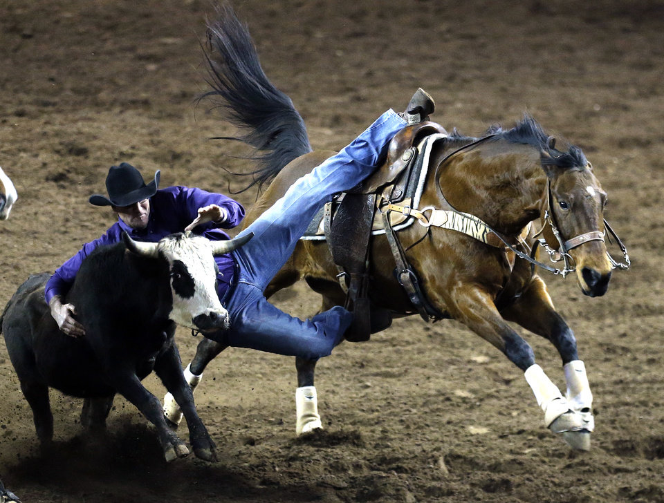 Photo - Jason Stewart of Bristow, Okla., rides Stevie in the steer wrestling competition during the International Finals Rodeo at the State Fair Arena in Oklahoma City, Friday, Jan. 17, 2014.  Photo by Sarah Phipps, The Oklahoman