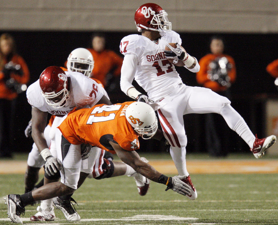 Photo - OU's Mossis Madu (17) is tripped up by OSU's Orie Lemon (41) in the fourth quarter during the Bedlam college football game between the University of Oklahoma Sooners (OU) and the Oklahoma State University Cowboys (OSU) at Boone Pickens Stadium in Stillwater, Okla., Saturday, Nov. 27, 2010. OU won, 47-41. Photo by Nate Billings, The Oklahoman