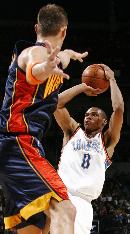 Photo - Oklahoma City's Russell Westbrook shoots over the defense of Golden State's Andris Biedrins in the first half during the NBA basketball game between the Golden State Warriors and the Oklahoma City Thunder at the Ford Center in Oklahoma City, Monday, December 8, 2008. BY NATE BILLINGS, THE OKLAHOMAN