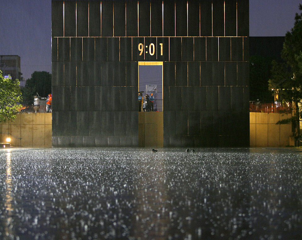 Photo - Rain falls on the Reflecting Pool at the Oklahoma City Memorial and Museum during the 11th Annual Oklahoma City Memorial Marathon in Oklahoma City on Sunday, May 1, 2011. The start of the races were delayed 3o minutes due to the weather. Photo by John Clanton, The Oklahoman