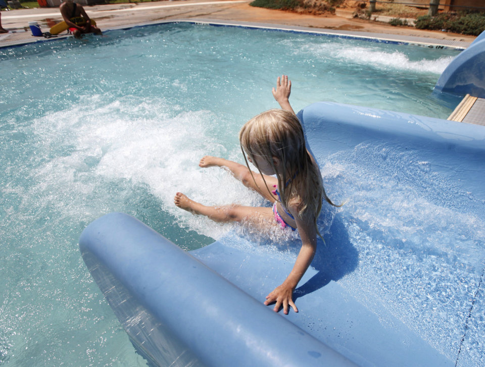 Photo -  Kendall Kingry, 5, flies off of one of the water slides at Pelican Bay Aquatic Center in Edmond. Photo by Paul Hellstern, The Oklahoman   PAUL HELLSTERN -