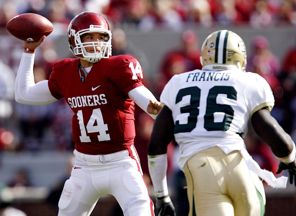 Photo - Oklahoma's Sam Bradford (14) throws a pass under the pressure of Chris Francis (36) during the first half of the college football game between the University of Oklahoma Sooners (OU) and the Baylor University Bears at Gaylord Family-Oklahoma Memorial Stadium on Saturday, Oct. 10, 2009, in Norman, Okla. 