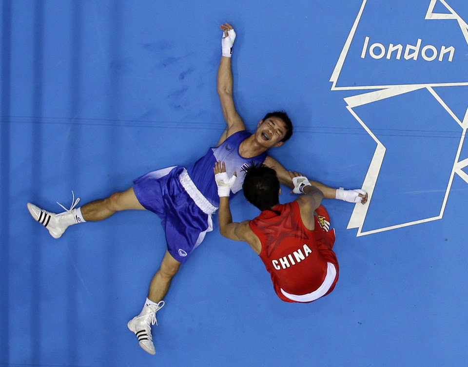 Photo -   Thailand's Kaeo Pongprayoon, in blue, lies on the mat after losing to China's Zou Shiming in the men's light flyweight 49kg boxing gold medal match at the 2012 Summer Olympics, Saturday, Aug. 11, 2012, in London. (AP Photo/Mark Duncan)