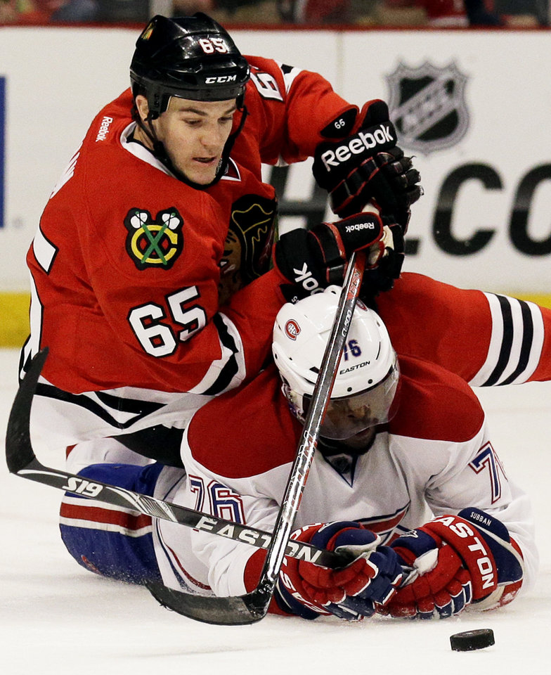 Photo - Chicago Blackhawks' Andrew Shaw (65), top, battles for the puck against Montreal Canadiens' P.K. Subban (76) during the second period of an NHL hockey game in Chicago, Wednesday, April 9, 2014. (AP Photo/Nam Y. Huh)