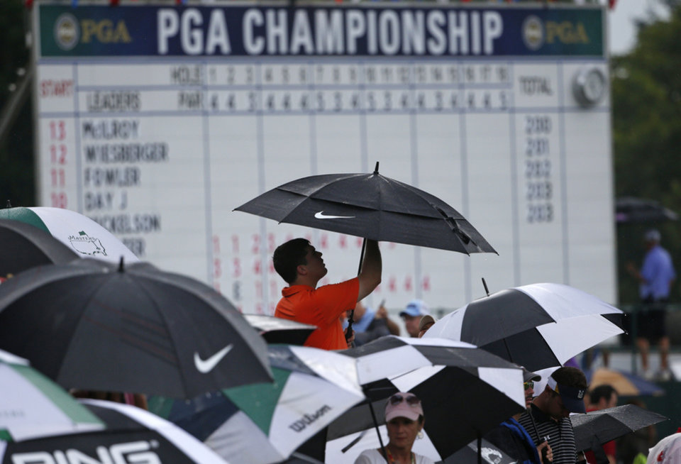 Photo - A golf fan puts up an umbrella during a rain delay during the final round of the PGA Championship golf tournament at Valhalla Golf Club on Sunday, Aug. 10, 2014, in Louisville, Ky. (AP Photo/Mike Groll)
