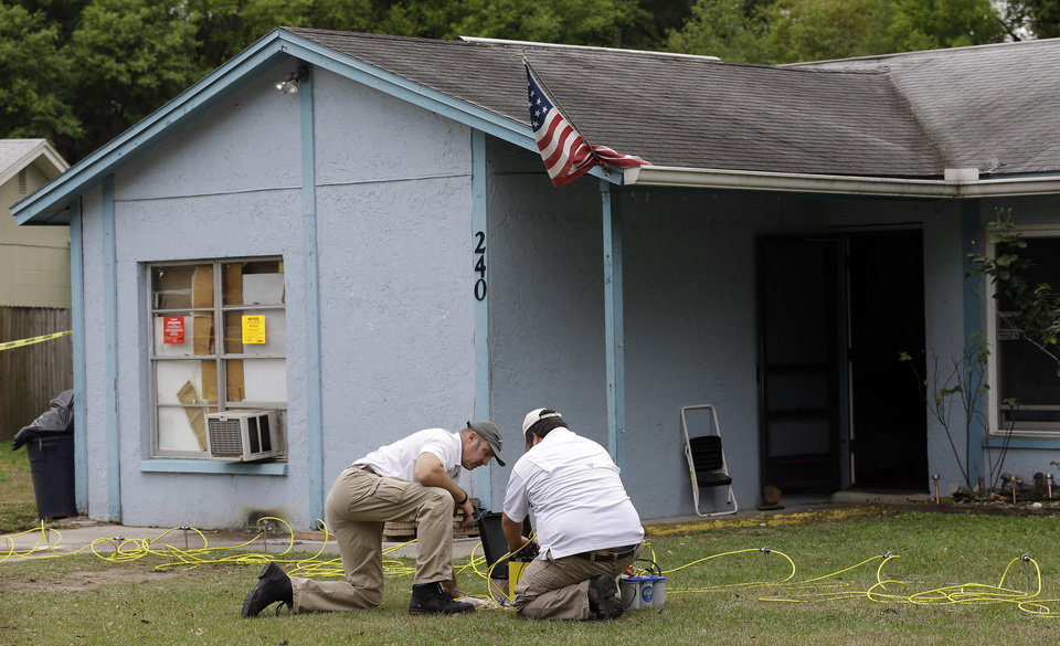 Engineers work in front of a home where sinkhole opened up underneath a bedroom and swallowed a man Friday, March 1, 2013, in Seffner, Fla. Jeff Bush screamed for help and disappeared as a large sinkhole opened under the bedroom of his house, his brother said Friday. Jeremy Bush told rescue crews he heard a loud crash near midnight Thursday, then heard his brother screaming.  There's been no contact with Jeff Bush since then, and neighbors on both sides of the home have been evacuated. (AP Photo/Chris O'Meara)