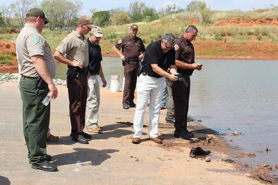 Photo - OKLAHOMA STATE BUREAU OF INVESTIGATION / MISSING BODIES FOUND: OSBI Special Agent Danny Sanders photographs a shoe discovered in Foss Lake, believed to be from one of two submerged vehicles pulled out of the lake today. Photo by Larissa Graham,The Elk City News