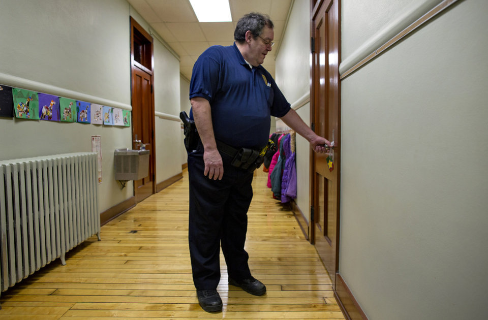 FILE - In this file photo of Jan. 14, 2013, New Washington, Ohio, Chief of Police Scott Robertson checks a teacher's door to make sure it's locked during a lockdown drill at the St. Bernard School in New Washington, Ohio, a month after the Sandy Hook Elementary School massacre in Newtown, Conn., that killed 26 people in December. Inspired by the memories of those who lost their lives, St. Bernard School's principal decided to hold lockdown drills on the 14th of each month to refine a safety plan and increase school security. (AP Photo/Craig Ruttle, File)