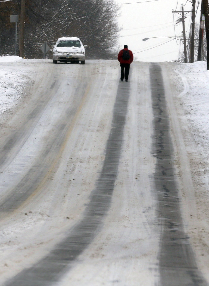 Photo - A pedestrian walks in the middle of a road to avoid snow covered sidewalks Tuesday, Jan. 21, 2014, in Cincinnati. The Cincinnati area received around three to five inches of snow. (AP Photo/Al Behrman)