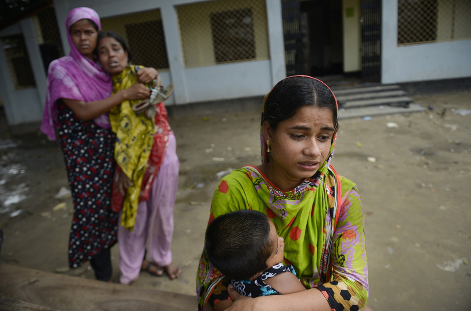Photo - A Bangladeshi woman holds the child of her dead sister, as another pair mourn for their dead sister, both victims of a building collapse, at a makeshift morgue in Savar near Dhaka, Bangladesh, Wednesday May 8, 2013. Dozens of bodies recovered Wednesday from the building were so decomposed they were being sent to a lab for DNA identification, police said, as the death toll from Bangladesh's worst industrial disaster topped 800. (AP Photo/Ismail Ferdous)
