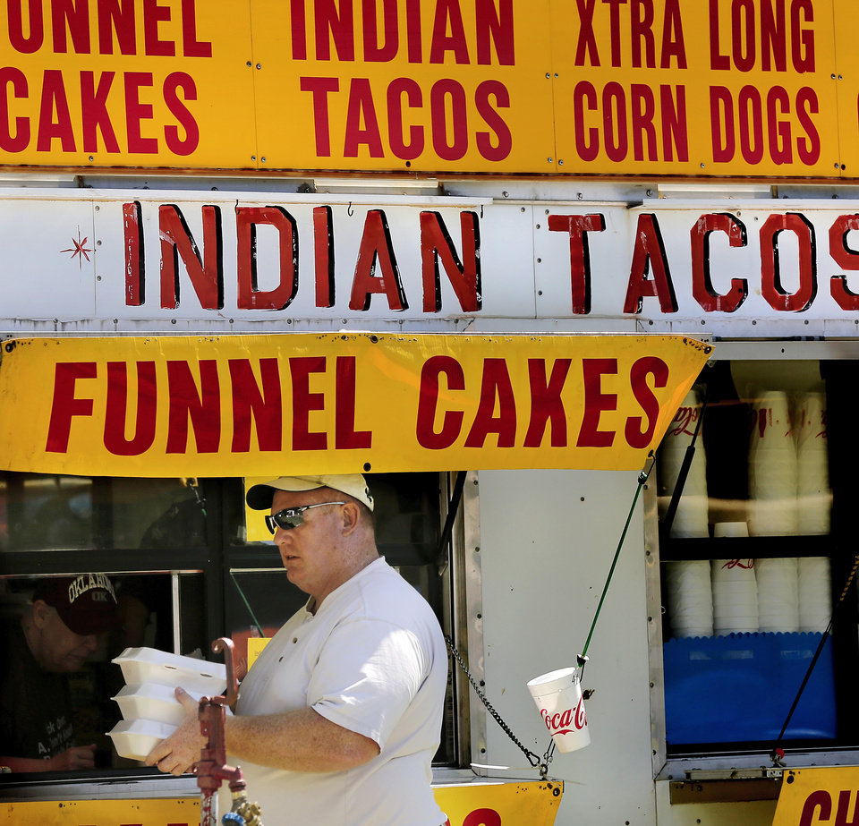 Photo -  A man walks away with boxes of Indian tacos he purchased during the Indian powwow at Joe B. Barnes Regional Park in Midwest City. Photo by Jim Beckel, The Oklahoman   Jim Beckel -