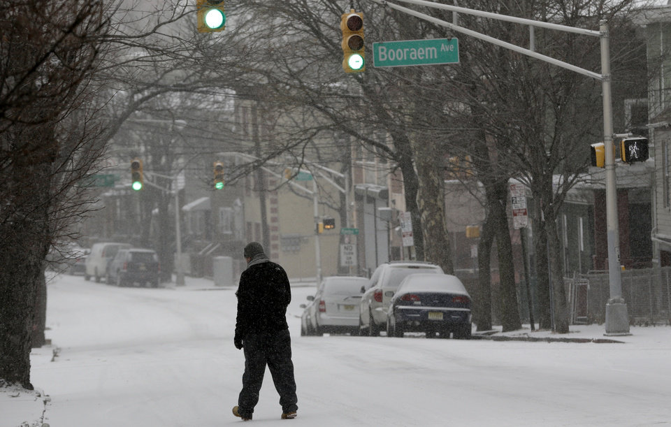 Photo - A man walks on a snow covered street, Tuesday, Jan. 21, 2014, in Jersey City, N.J. A storm is expected to hit the northern New Jersey region throughout the day. Because of hazardous driving conditions New Jersey Gov. Chris Christie's inauguration party at Ellis Island was cancelled. (AP Photo/Julio Cortez)