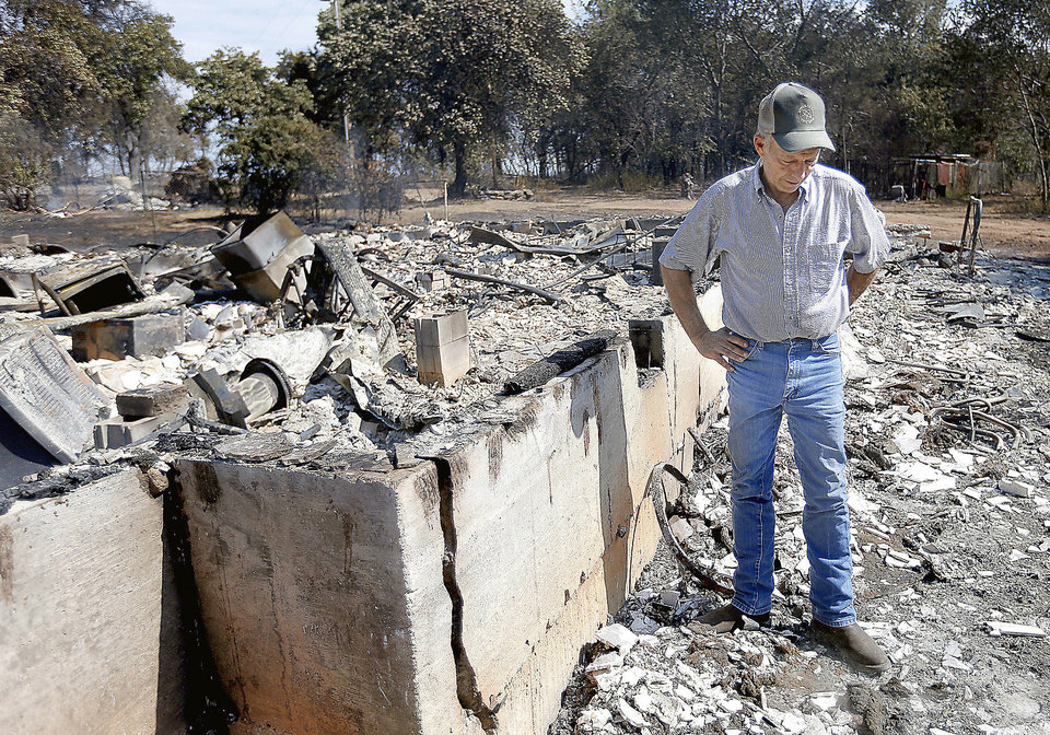 Photo - Doug Roberson looks over damage at the home of Oscar Montelongo on Sunday in Glencoe after wildfires moved through the area  Saturday. Photos by Sarah Phipps, The Oklahoman