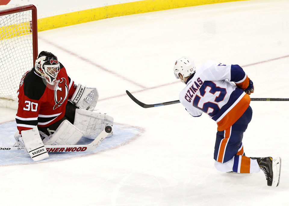 Photo - New Jersey Devils goalie Martin Brodeur (30) blocks a shot by New York Islanders center Casey Cizikas (53) during the third period of an NHL hockey game on Friday, April 11, 2014, in Newark, N.J. The Islanders won 3-2. (AP Photo/Julio Cortez)