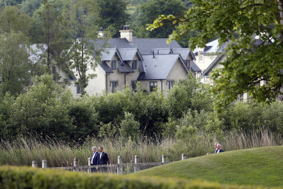 Photo - US President Barack Obama and Canadian Prime Minister Stephen Harper, left, walk to a group photo opportunity during the G-8 summit at the Lough Erne golf resort in Enniskillen, Northern Ireland, on Tuesday, June 18, 2013. The final day of the G-8 summit of wealthy nations is ending with discussions on globe-trotting corporate tax dodgers, a lunch with leaders from Africa, and suspense over whether Russia and Western leaders can avoid diplomatic fireworks over their deadlock on Syria's civil war. (AP Photo/Lefteris Pitarakis)