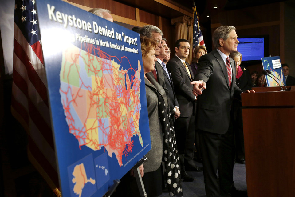 Photo - FILE - In this Jan. 23, 2013, file photo, Sen. John Hoeven, R-N.D, points at a illustration of existing pipeline, while speaking at a news conference about the Keystone XL oil pipeline on Capitol Hill in Washington. The State Department on Friday, March 1, 2013, raised no major objections to the Keystone XL oil pipeline and said other options to get the oil from Canada to U.S. Gulf Coast refineries are worse for climate change. But the latest environmental review stops short of recommending whether the project should be approved.  (AP Photo/Jacquelyn Martin, File)