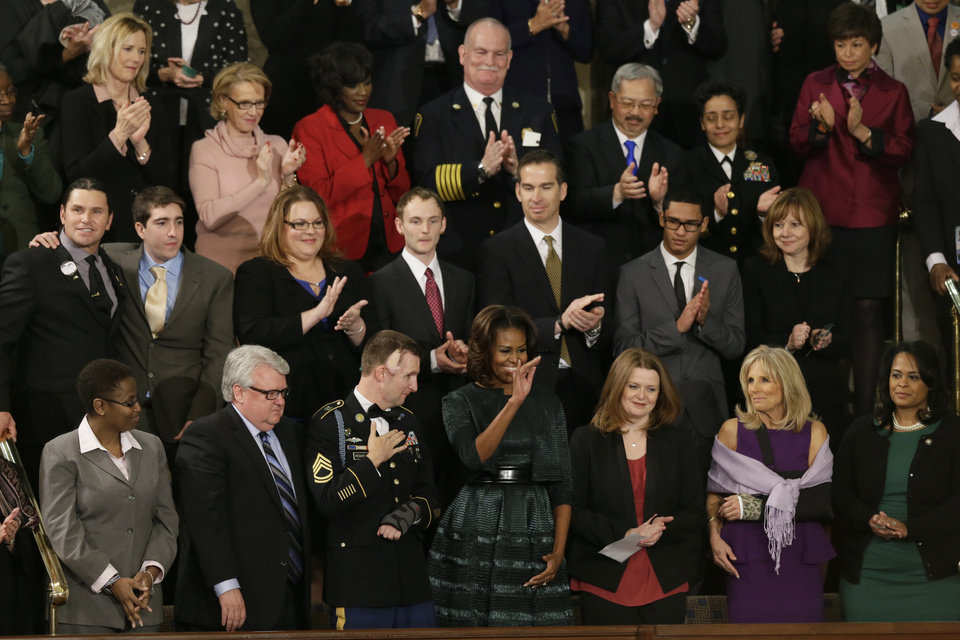 Photo - First Lady Michelle Obama waves from her box before President Barack Obama's State of the Union address on Capitol Hill in Washington, Tuesday Jan. 28, 2014. (AP Photo/J. Scott Applewhite)