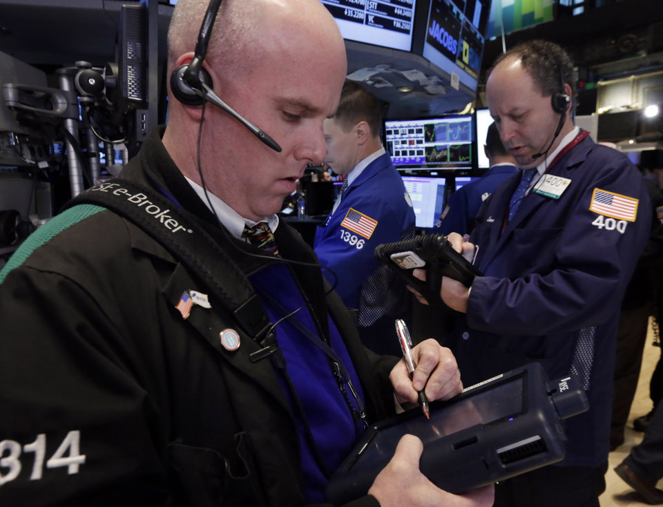 Photo - Traders Kevin Walsh, left, and Gordon Charlop work on the floor of the New York Stock Exchange Wednesday, April 30, 2014.  The stock market is edging lower Wednesday after the U.S. economy slowed more drastically in the first quarter than economists had believed. (AP Photo)