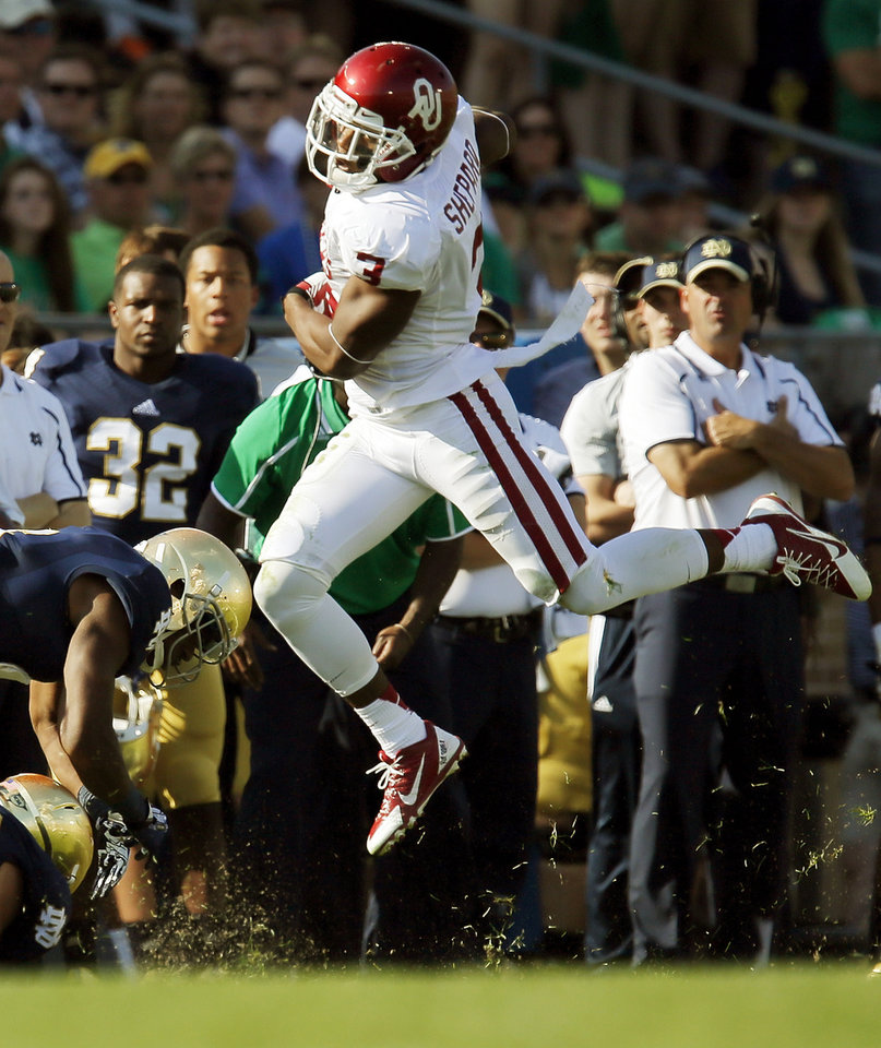 Photo - Oklahoma's Sterling Shepard (3) leaps while running after a catch in the second quarter during a college football game between the University of Oklahoma Sooners (OU) and the Notre Dame Fighting Irish at Notre Dame Stadium in South Bend, Ind., Saturday, Sept. 28, 2013. Photo by Nate Billings, The Oklahoman