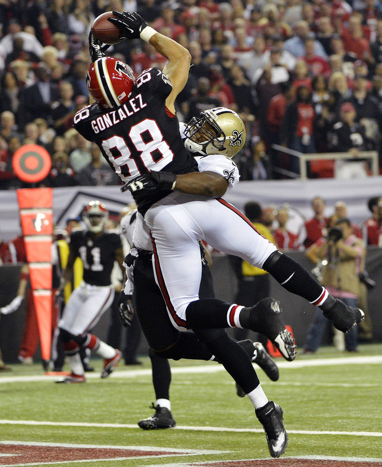 Photo - Atlanta Falcons tight end Tony Gonzalez (88) makes a catch for a touchdown as New Orleans Saints middle linebacker Curtis Lofton (50) defends during the first half of an NFL football game, Thursday, Nov. 29, 2012, in Atlanta. (AP Photo/Rich Addicks)