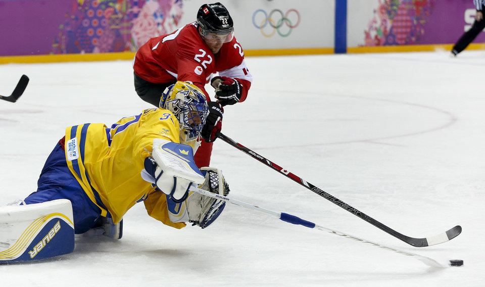 Photo - Sweden goaltender Henrik Lundqvist reaches to clear the puck away from Canada forward Jamie Benn during the second period of the men's gold medal ice hockey game at the 2014 Winter Olympics, Sunday, Feb. 23, 2014, in Sochi, Russia. (AP Photo/Julio Cortez)