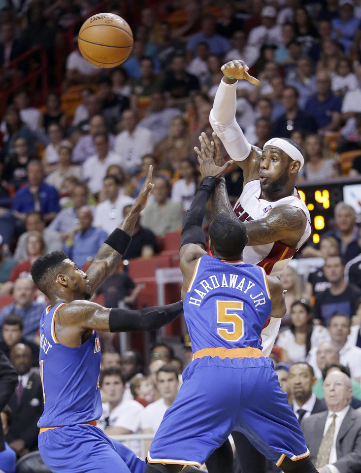 Photo - Miami Heat forward LeBron James passes past New York Knicks guard Iman Shumpert, left, and guard Tim Hardaway Jr. (5) during the first half of an NBA basketball game, Sunday, April 6, 2014, in Miami. (AP Photo/Wilfredo Lee)