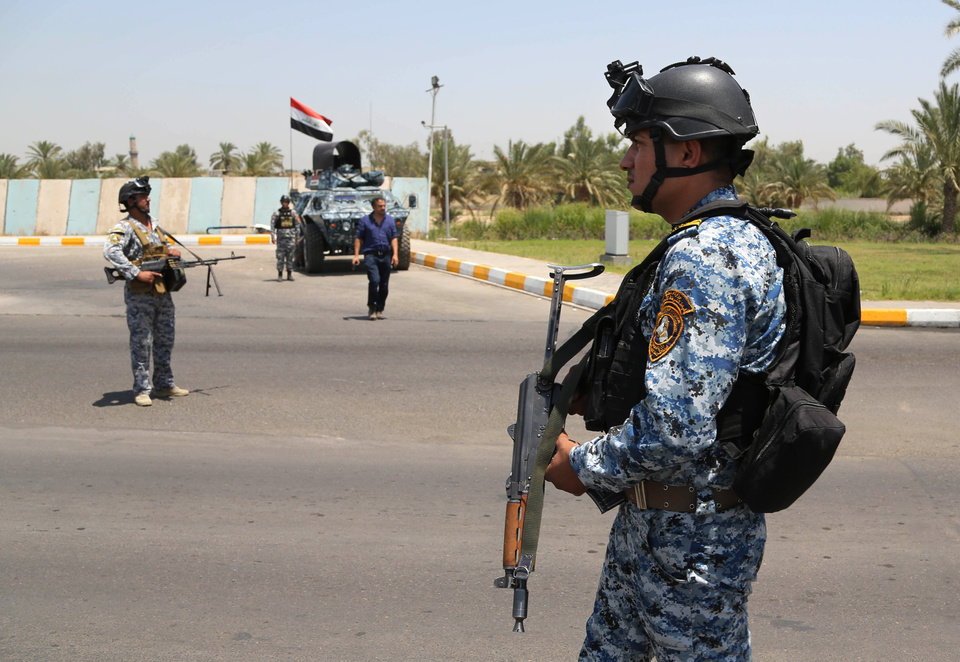 Photo - Iraqi federal policemen stand guard at a checkpoint outside of Baghdad International Airport, Iraq, Saturday, June 28, 2014. Iraqi troops backed by helicopter gunships launched an operation early Saturday aimed at dislodging Sunni militants from the northern city of Tikrit, one of two major urban centers they seized in recent weeks in a dramatic blitz across the country. (AP Photo/Karim Kadim)