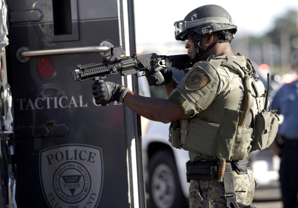Photo - A member of the St. Louis County Police Department points his weapon in the direction of a group of protesters in Ferguson, Mo. on Wednesday, Aug. 13, 2014. On Saturday, Aug. 9, 2014, a white police officer fatally shot Michael Brown, an unarmed black teenager, in the St. Louis suburb. (AP Photo/Jeff Roberson)