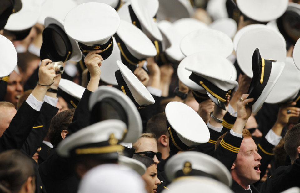 Photo -   Members of the Navy lifts their hats to support their team playing against Notre Dame during their NCAA college football game in Dublin, Ireland, Saturday, Sept. 1, 2012. (AP Photo/Peter Morrison)