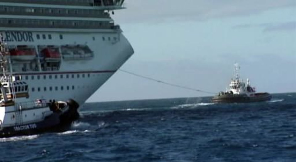 Photo - In this image taken from video, tug boats pull the disabled cruise ship Carnival  Splendor toward the U.S. Wednesday, Nov. 10, 2010. The boat is expected to dock in San Diego midday Thursday. (AP Photo/APTN)