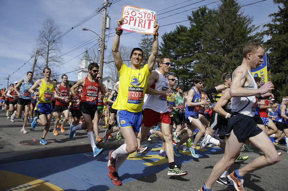Photo - Runners in the first wave of 9,000 cross the start line of the 118th Boston Marathon Monday, April 21, 2014 in Hopkinton, Mass.  (AP Photo/Stephan Savoia)